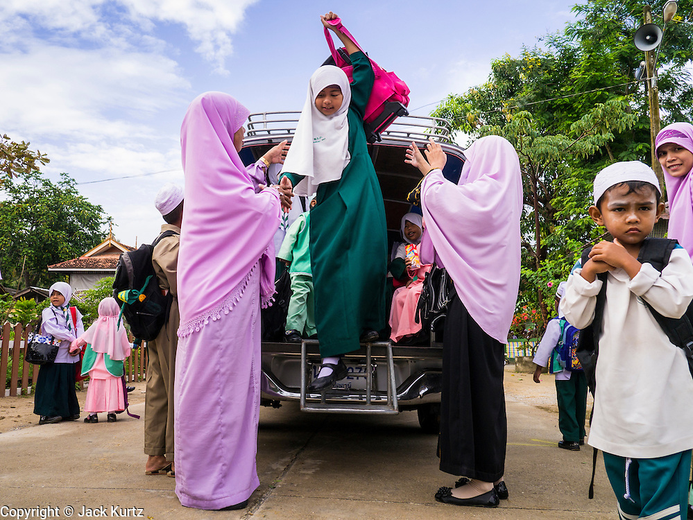 10 JULY 2013 - PATTANI, PATTANI, THAILAND: Students at a private Muslim school get out of a pickup truck used as a school bus in Pattani. Many Muslim parents prefer to send their children to Muslim private schools because they are safer (public schools have been attacked by Muslim insurgents), the Muslim schools teach an Islam centric curriculum and teach what many in Pattani consider a more accurate version of Pattani history.   PHOTO BY JACK KURTZ