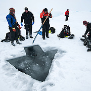 Shawn Harper and Kelly Nolan cut a triangle hole in the ice for dives beneath the Arctic Ocean ice pack.
