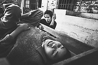 A woman sits vigil over a sick child at a small leprosy village in northern Shan State in Myanmar.
