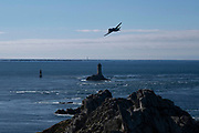 A vintage twin prop aeroplane flies past the rocky coastal landscape and lighthouses at the promontory of Pointe du Raz on 23rd September 2021 in Plogoff, Brittany, France. Brittany is a peninsula, historical county, and cultural area in the west of France, covering the western part of what was known as Armorica during the period of Roman occupation. It became an independent kingdom and then a duchy before being united with the Kingdom of France in 1532 as a province governed as a separate nation under the crown.