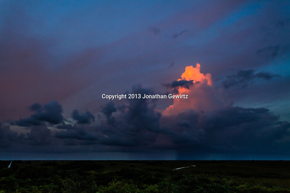 The last rays of the setting sun illuminate an isolated thunderstorm near the Shark Valley section of Everglades National Park, Florida.<br /> <br /> WATERMARKS WILL NOT APPEAR ON PRINTS OR LICENSED IMAGES.<br /> <br /> Licensing: https://tandemstock.com/assets/14364823
