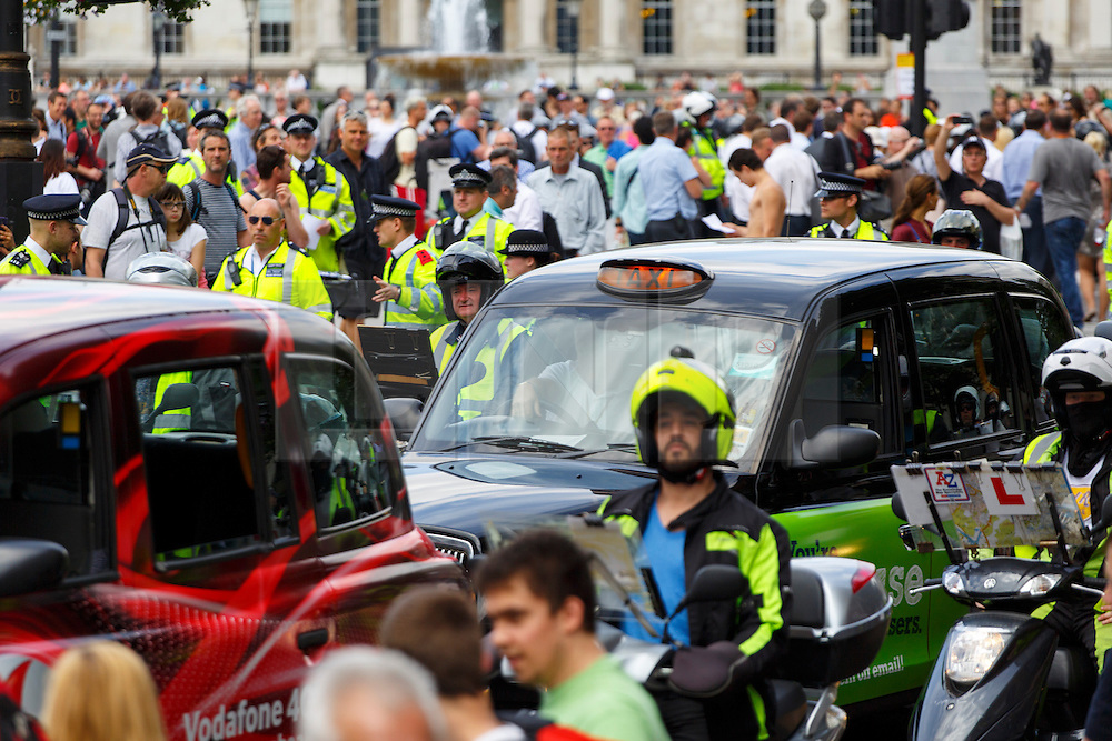 © Licensed to London News Pictures. 11/06/2014. LONDON, UK. Drivers of London black cabs gridlocking the area around Trafalgar Square, the Houses of Parliament and Whitehall in a protest against the Uber app-based service on Wednesday, 11 June 2014 in central London. The cabbies claim the app mini-cab service is threatening taxi jobs. Photo credit : Tolga Akmen/LNP