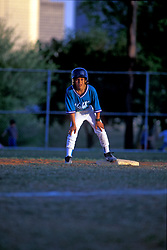 Stock photo of a boy on base waiting to run during a baseball game