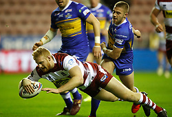 Wigan Warriors Joe Bullock goes over for a try past Leeds Rhinos Jack Walker during the Betfred Super League match at the DW Stadium, Wigan.