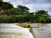 09 AUGUST 2018 - KAENG KRACHAN, PHETCHABURI, THAILAND: Flood water flows over a spillway at the Kaeng Krachan Dam. The Phetchaburi River flows from Kaeng Krachan Dam to the Gulf of Siam through several towns including Ban Lat, Phetchaburi (the capital of Phetchaburi province) and Ban Laem. Government officials have warned residents of those towns that their towns will flood because the reservoir behind the dam is approaching capacity. Ban Lat and Phetchaburi could be flooded for several weeks. Residents of Ban Laem have been warned that their community could be inundated for over a month. Dams in Kanchanaburi province, west of Phetchaburi, are also approaching capacity and flooding is also expected in that area.   PHOTO BY JACK KURTZ