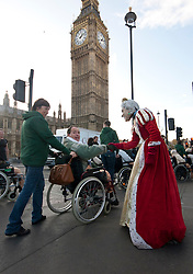 © licensed to London News Pictures. London, UK 30/11/11. As medical workers passing the Westminster Bridge to attend the main march in London, a patient shakes hand with a tourist entertainer who poses as the Queen. Photo credit: Tolga Akmen/LNP