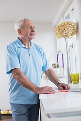 Smiling senior man looking out of window