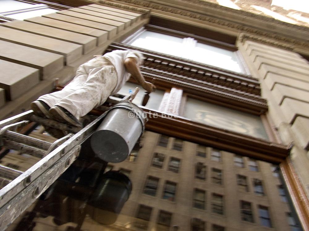 a painter working high up a ladder