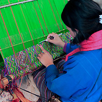 Asia, Bhutan, Paro. Bhutanese woman weaves traditional kira.