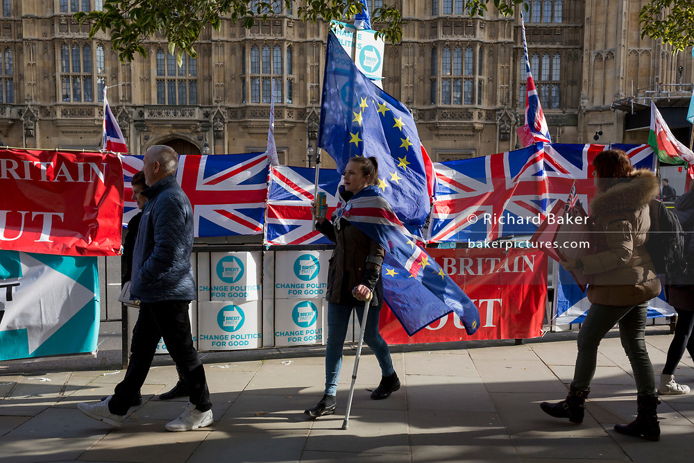 On the day that the EU in Brussels agreed in principle to extend Brexit until 31st January 2020 (aka 'Flextension') and not 31st October 2019, a Remainer lady carries an EU flag past Brexit Party flags and banners during a Brexit protest outside parliament, on 28th October 2019, in Westminster, London, England.