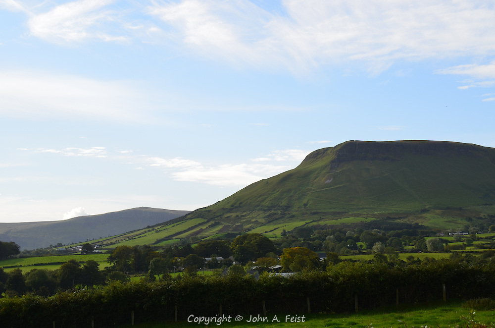 A view of some of the farmland and the cliffs going down to the sea in Cushendall, County Antrim, Northern Ireland.  The sun was shining over cliffs, but where I stood was overcast and rainy.
