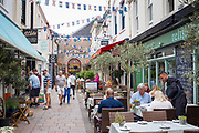 Locals and tourists in pavement cafes and artisan shops in Halkett Street by St Helier Central Market in Jersey, Channel Isles