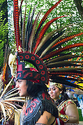 Dancers in colorful full costumes and elaborate headdresses made of feathers perform at the 2015 May Day Rally in Portland, Oregon