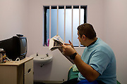 A prisoner reading a newspaper in his cell. HMP Wandsworth, London, United Kingdom