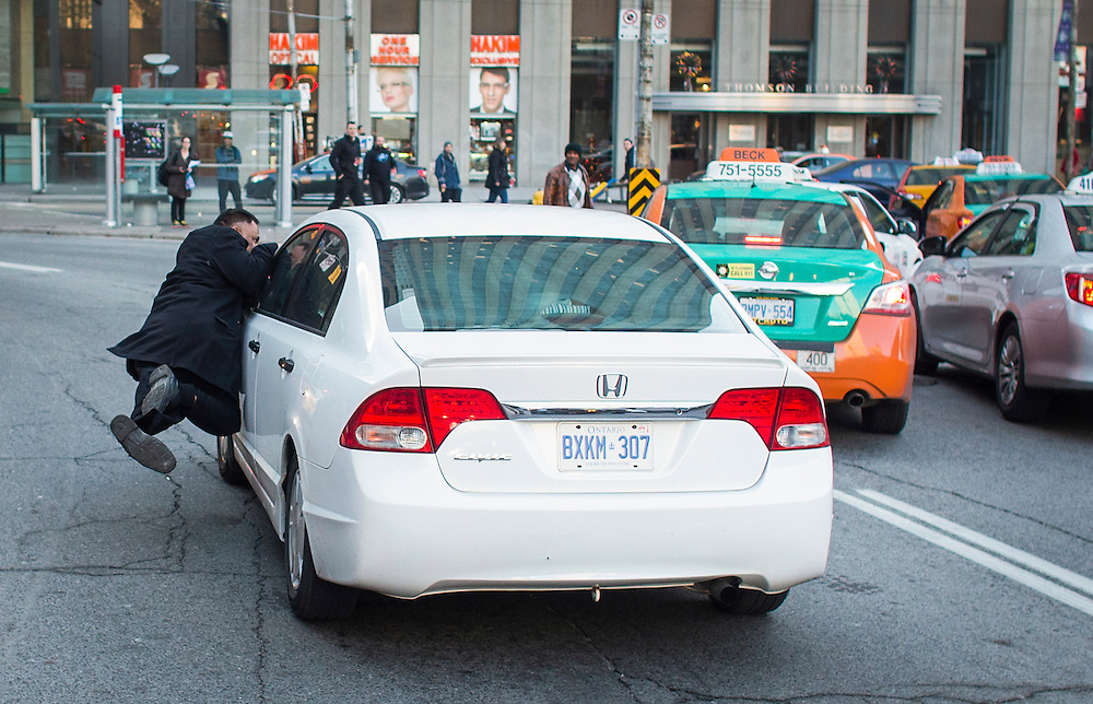 Toronto taxi driver Suntharesan Kanagasabai accuses the driver of the moving car he is hanging to of being an Uber driver, during a protest against Uber in Toronto, Wednesday December 9, 2015.