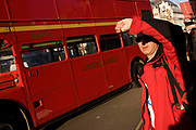 As a red London bus passes-by, a tourist wearing a matching red jacket shields his face from sunshine. The bus is a traditional design called a Routemaster which has been in service on the capital's roads since 1954 and is nowadays only seen on heritage routes. From any angle, the bus is easily recognisable as that classic British transport icon.
