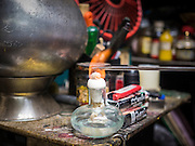 """25 MAY 2015 - BANGKOK, THAILAND: A tattoo needle is sterilized in a flame in Ajarn Neng Onnut's Sak Yant tattoo parlor. Sak Yant (Thai for """"tattoos of mystical drawings"""" sak=tattoo, yantra=mystical drawing) tattoos are popular throughout Thailand, Cambodia, Laos and Myanmar. The tattoos are believed to impart magical powers to the people who have them. People get the tattoos to address specific needs. For example, a business person would get a tattoo to make his business successful, and a soldier would get a tattoo to help him in battle. The tattoos are blessed by monks or people who have magical powers. Ajarn Neng, a revered tattoo master in Bangkok, uses stainless steel needles to tattoo, other tattoo masters use bamboo needles. The tattoos are growing in popularity with tourists, but Thai religious leaders try to discourage tattoo masters from giving tourists tattoos for ornamental reasons.       PHOTO BY JACK KURTZ"""