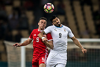 """Luis Suarez, right, of Uruguay national football team heads the ball to make a pass against James Chester of Wales national football team in their final match during the 2018 Gree China Cup International Football Championship in Nanning city, south China's Guangxi Zhuang Autonomous Region, 26 March 2018.<br /> <br /> Edinson Cavani's goal in the second half helped Uruguay beat Wales to claim the title of the second edition of China Cup International Football Championship here on Monday (26 March 2018). """"It was a tough match. I'm very satisfied with the result and I think that we can even get better if we didn't suffer from jet lag or injuries. I think the result was very satisfactory,"""" said Uruguay coach Oscar Tabarez. Wales were buoyed by a 6-0 victory over China while Uruguay were fresh from a 2-0 win over the Czech Republic. Uruguay almost took a dream start just 3 minutes into the game as Luis Suarez's shot on Nahitan Nandez cross smacked the upright. Uruguay were dealt a blow on 8 minutes when Jose Gimenez was injured in a challenge and was replaced by Sebastian Coates. Inter Milan's midfielder Matias Vecino of Uruguay also fired at the edge of box from a looped pass but only saw his attempt whistle past the post. Suarez squandered a golden opportunity on 32 minutes when Ashley Williams's wayward backpass sent him clear, but the Barca hitman rattled the woodwork again with goalkeeper Wayne Hennessey well beaten."""
