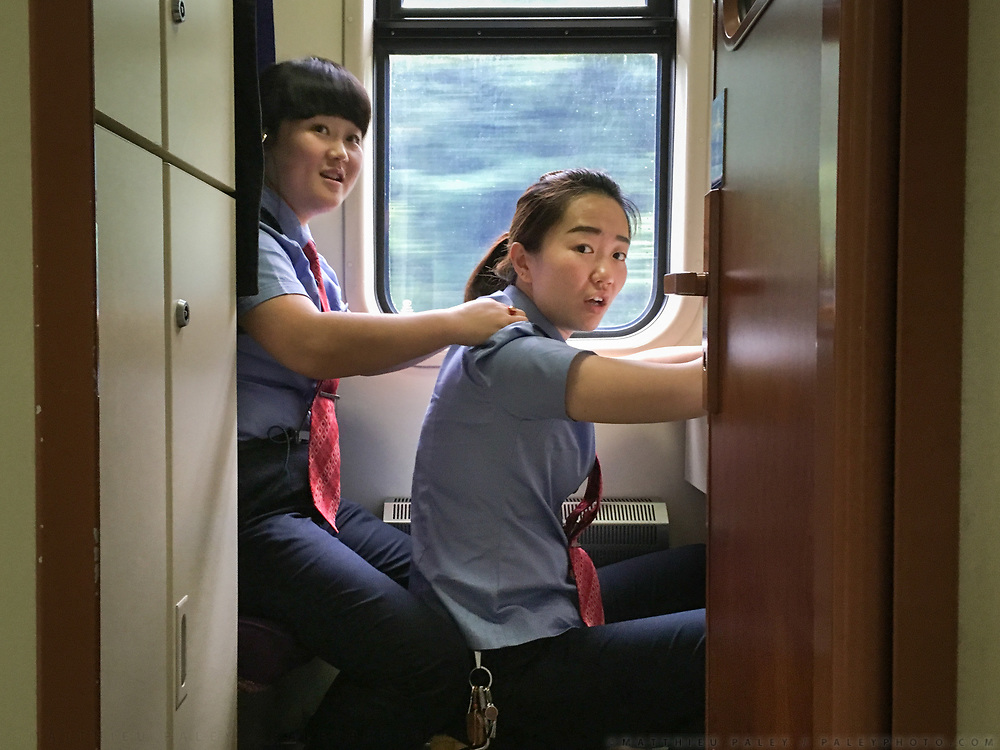 Staff give eachother a massage during a break. Between Zhuzhou and Shangsha. Life in the train from Hong Kong to Urumqi, Xinjiang.