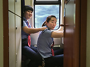 Staff give eachother a massage during a break. Between Zhuzhou and Shangsha. Life in the train from Hong Kong to Urumqi, Xinjiang.