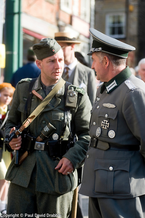 """Two re-enactors portraying a German soldier with MP40 submachine gun and """"potato Masher"""" stick grenade (left) chats to a German Officer chat on the streets of Pickering during the 1940s war weekend October 2009 Image Copyright Paul David Drabble"""