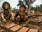 Brother and sister make mud bricks in wooden frame for parents house, Arun valley, Nepal