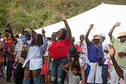 """The crowd puts their hands up for Cool Session Brass.  The University of the Virgin Islands hosts """"A Centennial Celebration of Delicacies for the Afternoon on the Green 2017 in celebration of the Virgin Islands Centennial and UVI's 55th anniversary.  Herman E. Moore Golf Course.  University of the Virgin Islands.  19 March 2017.  © Aisha-Zakiya Boyd"""