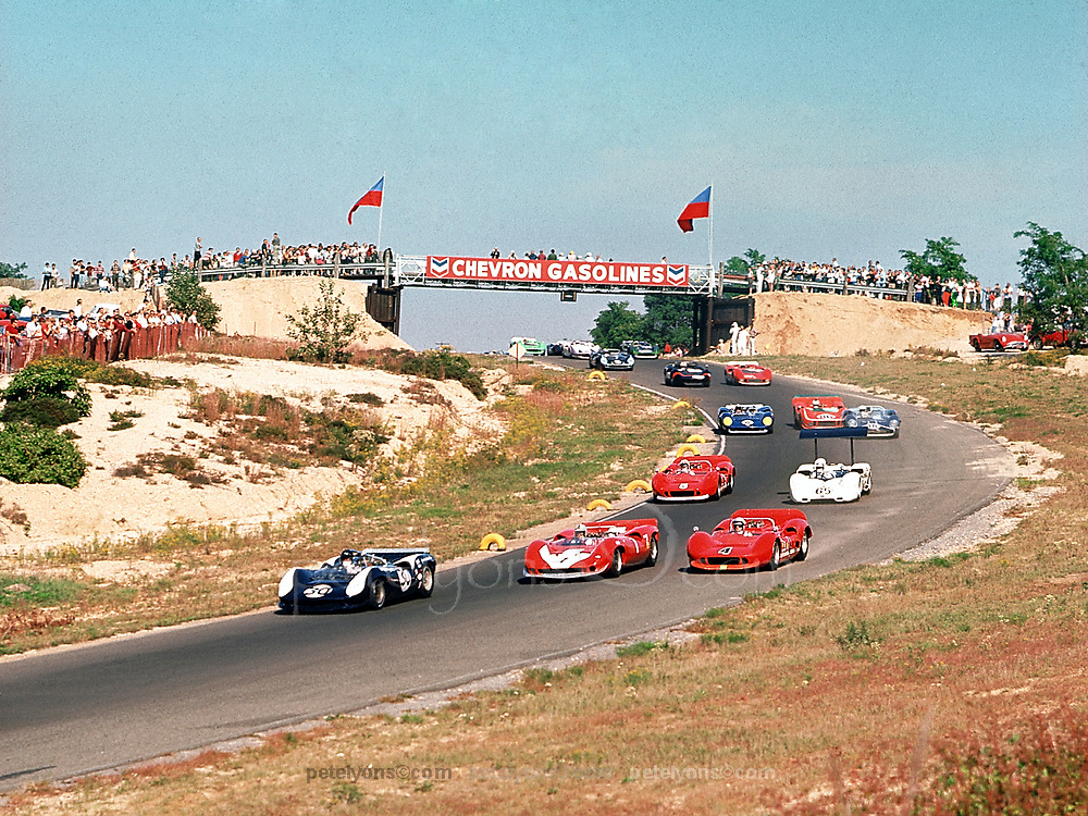 Dan Gurney (Lola 30) paces pack before start of 1966 Bridgehampton Can-Am, a race he would win; alongside on front row are John Surtees (Lola 7), Bruce McLaren (McLaren 4); in 2nd row are Chris Amon (who would finish a close 2nd in McLaren 5) and Phil Hill (making series debut of Chaparral no 65); then Mark Donohue (Lola 6).