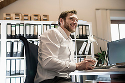 Mid adult businessman drinking coffee in an office and smiling, Bavaria, Germany