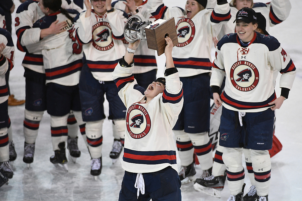 ERIE, PA - MARCH 06: Wasyn Rice #7 of the Robert Morris Colonials hoists the CHA Championship Trophy after the Colonials defeated the Syracuse Orange 1-0 in the championship game at the Erie Insurance Arena on March 6, 2021 in Erie, Pennsylvania. (Photo by Justin Berl/Robert Morris Athletics)
