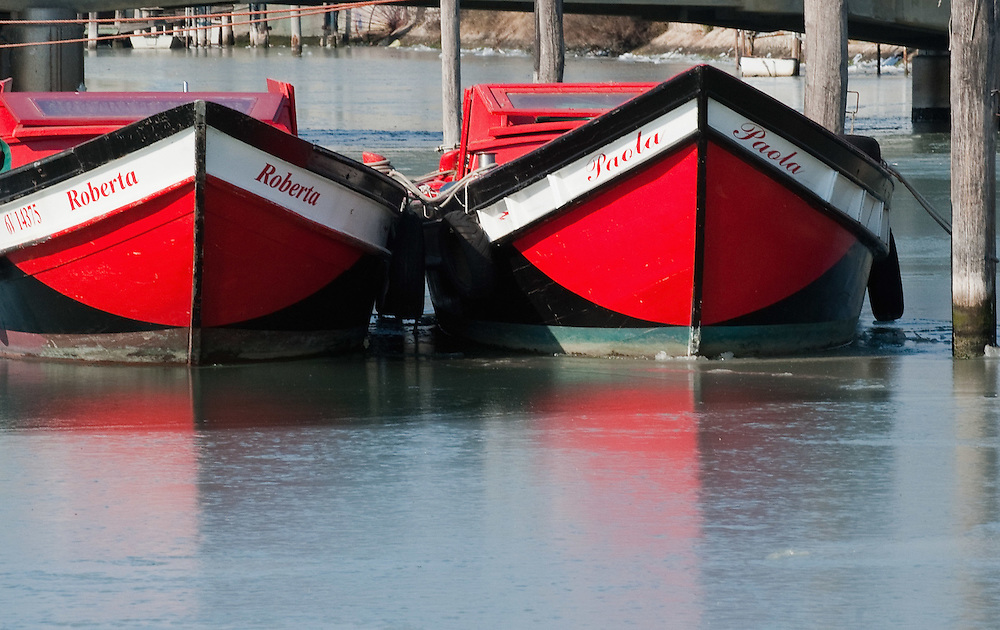 VENICE, ITALY - FEBRUARY 05: Two red boats are nearly blocked by ice in the North side of the frozen Venice Lagoon on February 5, 2012 in Venice, Italy. Italy as most of Europe is under a spell of very cold weather, it is more than 20 years aince the Venice Lagoon last froze.  (Photo by Marco Secchi/Getty Images)