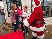 "30 NOVEMBER 2019 - WEST DES MOINES, IOWA: SANTA CLAUS talks to people on Elm Street in West Des Moines, Saturday. Santa was handing out gifts to children on Small Business Saturday. ""Small Business Saturday"" was first observed in the United States on November 27, 2010, as a counterpart to Black Friday and Cyber Monday, which are generally considered events at malls, ""big box"" stores and e-commerce retailers. Small Business Saturday encourages holiday shoppers to patronize brick and mortar businesses that are small and local. Small Business Saturday is a registered trademark of American Express.     PHOTO BY JACK KURTZ"