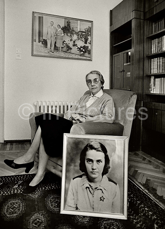 """Known as the """"Black Widow of the Balkans"""", Nexhmije Hoxha, the wife of the Albanian communist dictator Enver Hoxha, at home in Tirana  under house arrest. In the foreground is an early photograph of herself as a young pioneer. At the age of 20, Nexhmije joined the Albanian communist party and rapidly rose in the party hierarchy thanks to her close relationship with the party leader Qemal Stafa. After his assassination during the World War II, Nexhmije married his successor Enver Hoxha."""
