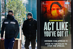 © Licensed to London News Pictures. 22/01/2021. London, UK. Men wearing protective face coverings walk past the government's 'Act Like You've Got It' publicity campaign poster in north London. The Office for National Statistics (ONS) has released figures which show the percentage of people testing positive for the virus decreased slightly in the week ending 16 January. During that period, an estimated one in 30 people had Covid-19 in London. Photo credit: Dinendra Haria/LNP
