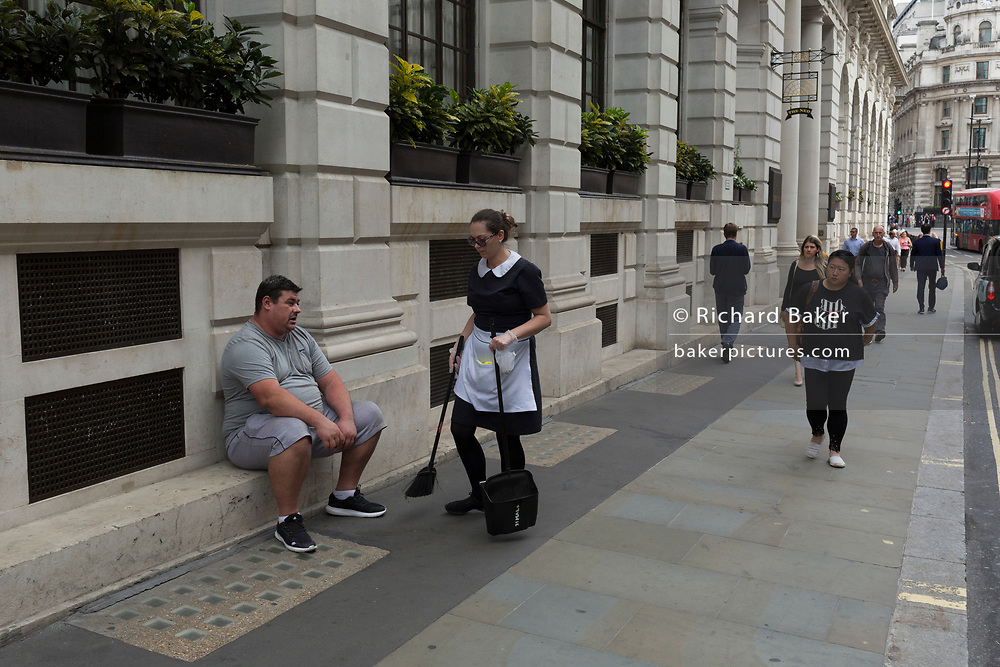 An female employee sweeps up litter from around the feet of an overweight man sitting outside The Ned Hotel in Poultry (street) in the City of London - the capital's financial district, on 3rd September 2018, in London England.