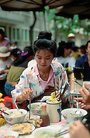 May 1993, Ho Chi Minh City, Vietnam --- Asian Woman Eating With Chopsticks --- Image by © Owen Franken