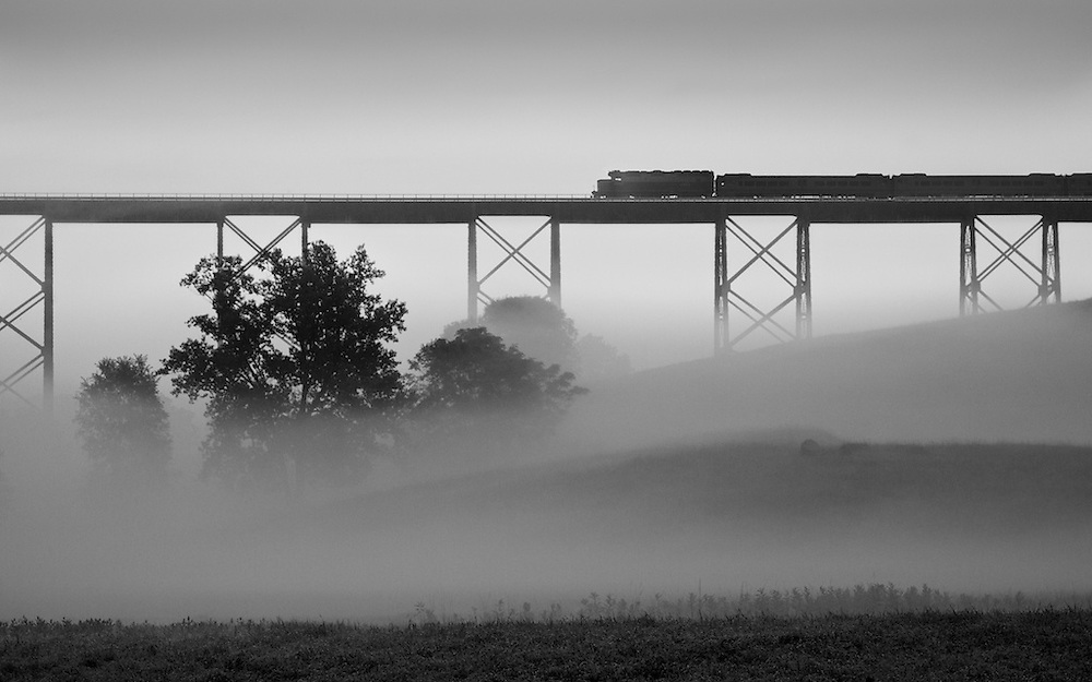 Its going to be a hot and humid day and as the sun rises, it hits the cool valley air beneath Moodna Viaduct and crates flash fog that lasts about 15 minutes. During this brief period, the momentary solitude and serenity is interrupted by a passing commuter train bound for Hoboken.