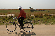 Jon Dwo, rides his bicycle by an abandon russian jet, by the road between Bor and Malakal cities in South Sudan as a reminder of the long years of civil war between north and south.  (PHOTO: MIGUEL JUAREZ LUGO)