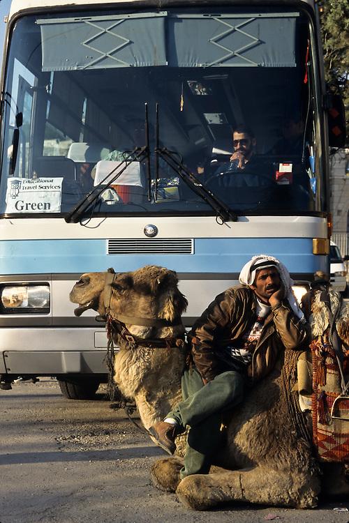 A man on a camel next to a tourist bus in Jerusalem.