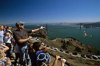 Golden Gate Rapter Observatory team member Jeremy Johnstone releasing a red-shouldered hawk (Buteo lineatus) for Marin Horizon School's 1st grade class.  Hawk Hill, Marin Headlands, California.  Oct 2002.