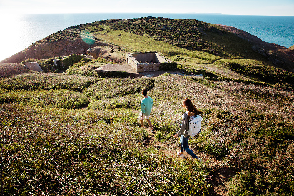Couple walking and exploring the cliff paths near Plemont and a German bunker up on the headland on a sunny summer day in Jersey. Channel Islands