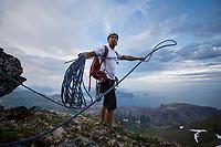 Male climber prepares rope for rappel from summit of Stjerntind mountai peak, Flakstadøy, Lofoten Islands, Norway
