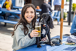 Licensed to London News Pictures. 12/04/2021. London, UK. Pub goers (left) Gabriella Lucena 24 with 1 year old Lola a Cocker Spaniel enjoy a pint and a soft drink along the Thames at Hammersmith, West London for the fist time in months as pubs and shops across England welcome back customers after Covid-19 restrictions were lifted today. Prime Minister Boris Johnson announced last week that non-essential shop, restaurants with outside seating , hairdressers and gyms can reopen today after 4 months of Covid-19 lockdowns. Photo credit: Alex Lentati/LNP