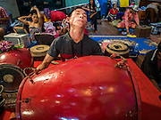 """30 JANUARY 2016 - NONTHABURI, NONTHABURI, THAILAND:  A musician performs while other members of the cast put on their makeup during a """"likay"""" show at Wat Bua Khwan in Nonthaburi, north of Bangkok. Likay is a form of popular folk theatre that includes exposition, singing and dancing in Thailand. It uses a combination of extravagant costumes and minimally equipped stages. Intentionally vague storylines means performances rely on actors' skills of improvisation. Like better the known Chinese Opera, which it resembles, Likay is performed mostly at temple fairs and privately sponsored events, especially in rural areas. Likay operas are televised and there is a market for bootleg likay videos and live performance of likay is becoming more rare.    PHOTO BY JACK KURTZ"""