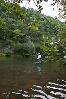 FLY ANGLER CATCHING A TROUT FROM THE MOUNTAIN FORK RIVER NEAR BROKEN BOW OKLAHOMA