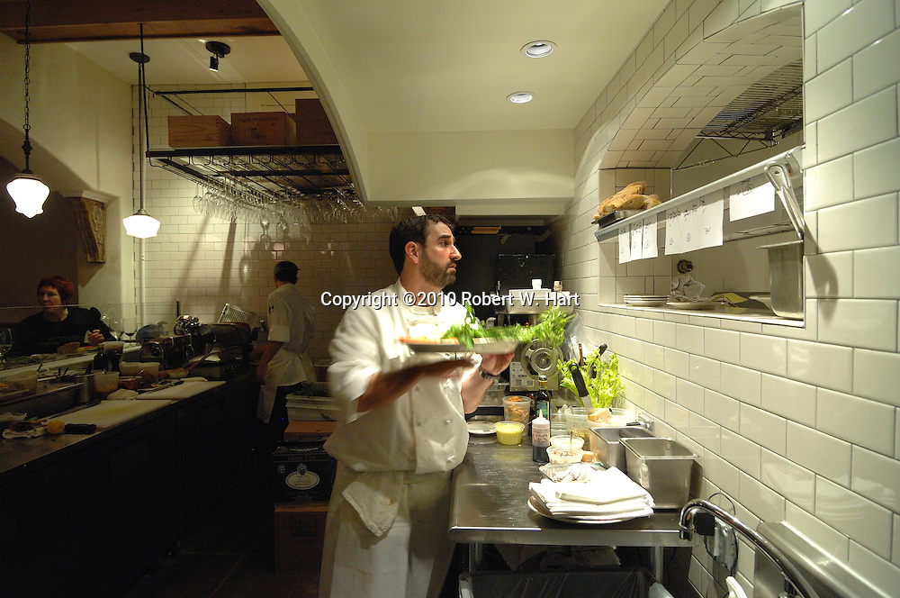 Lucia restaurant owner and chef, David Uygur, takes a dish from the kitchen on Tuesday evening Dec. 14, 2010 at 408 W. 8th. St., in the Bishop Arts District of Dallas' Oak Cliff neighborhood.