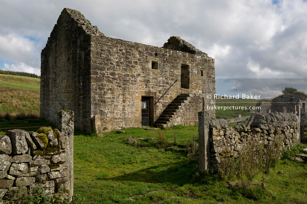 Exterior of the best preserved Grade 2 listed Bastle (a fortified 18th/19th century farmhouse) at Black Middens, on 28th September 2017, in Gatehouse, Northumberland, England. Bastel, bastle, or bastille houses are a type of construction found along the Anglo-Scottish border, in the areas formerly plagued by border Reivers. Typically, the bastle was 10-12 metres long by 5-6 metres wide with walls up to 1.6 metres thick. Some 400 tonnes of sandstone blocks were needed for construction with corner quoins (corner stones) weighing up to 300kg. Bastles would have been costly to build so afforded by only wealthy families fearing attack by cross-border bandits.