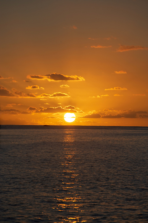 St. Barth ocean sunset with beautiful clouds and reflection in water