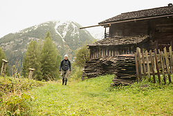 Mature hiker passing by cottage at rainy day, Austrian alps, Carinthia, Austria