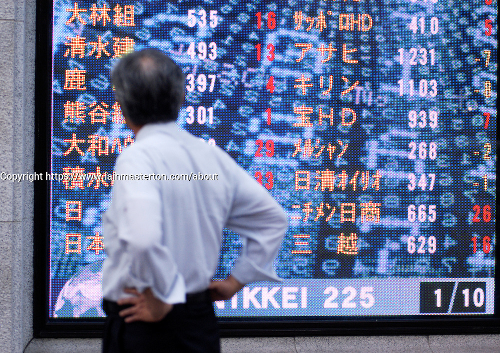 Man checking stock prices on large television monitor in central Tokyo